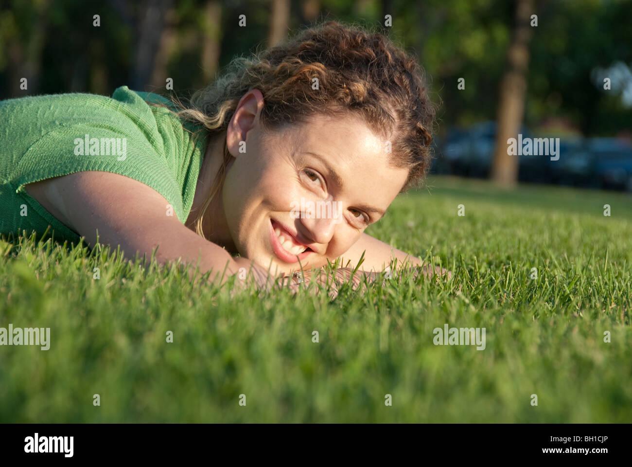 Mujer sonriente en el césped, Assiniboine Park, Winnipeg, Manitoba, Canadá Imagen De Stock