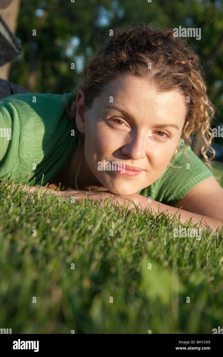 Retrato de mujer en sus 40s sobre el césped en el Parque Assinboine, Winnipeg, Manitoba, Canadá Imagen De Stock