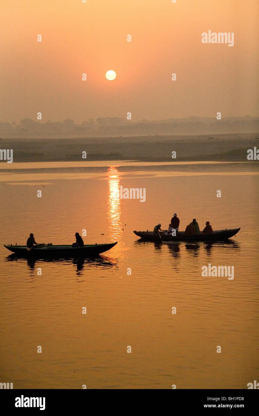 Los barcos son remé como el sol se eleva por encima del río Ganges (Ganga) en Varanasi en Uttar Prdesh, Imagen De Stock