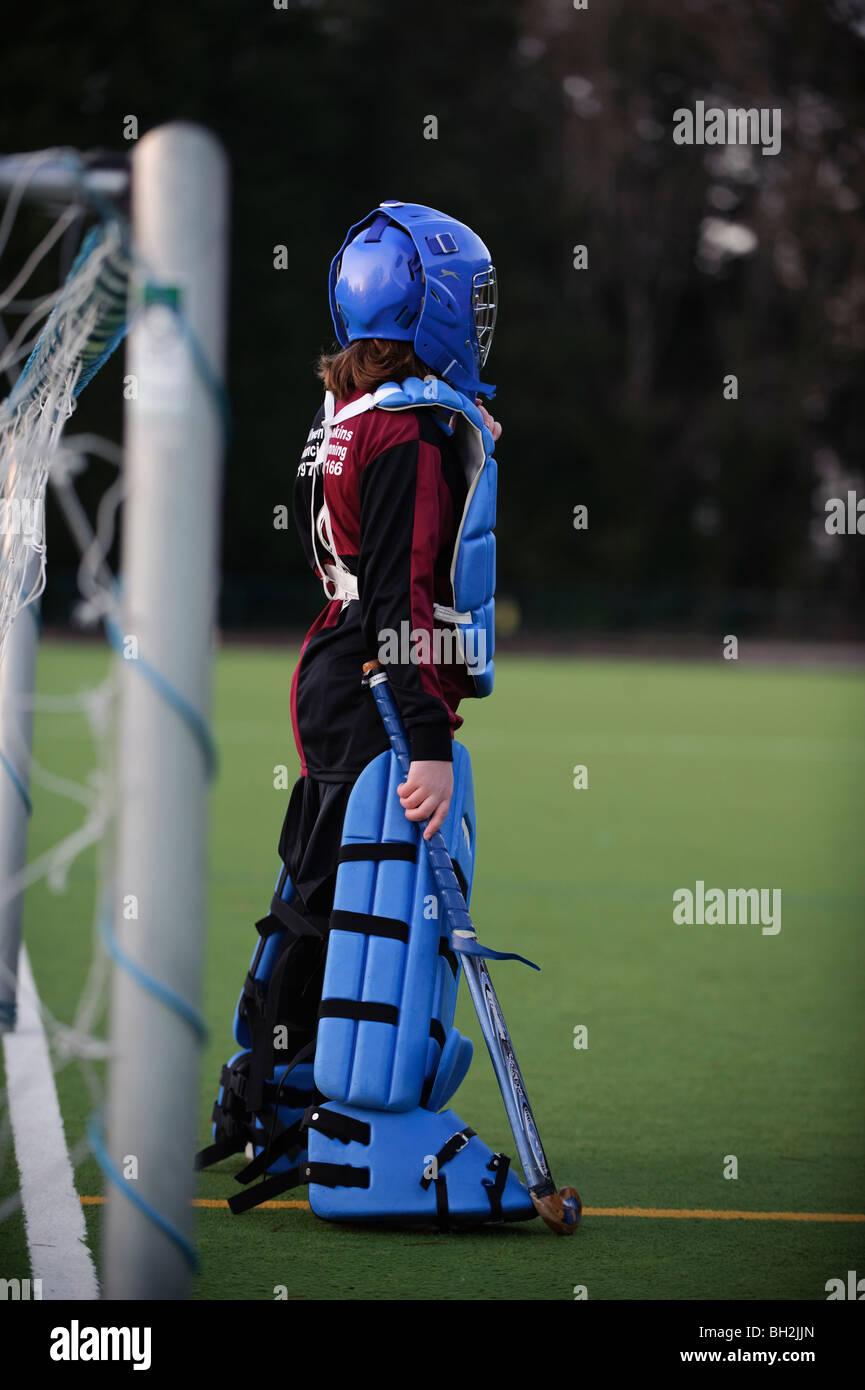 11 años de edad, niña vistiendo almohadilladas en la meta jugando al hockey sobre superficie de todo tiempo, Imagen De Stock