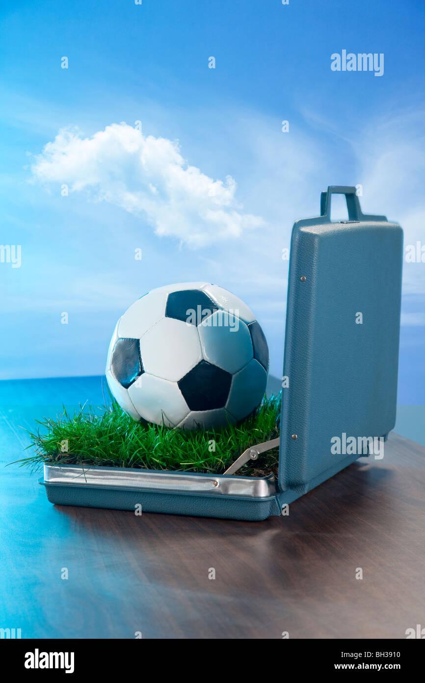 Abra Mi Maletín en el escritorio con una pelota de fútbol y la hierba dentro Imagen De Stock
