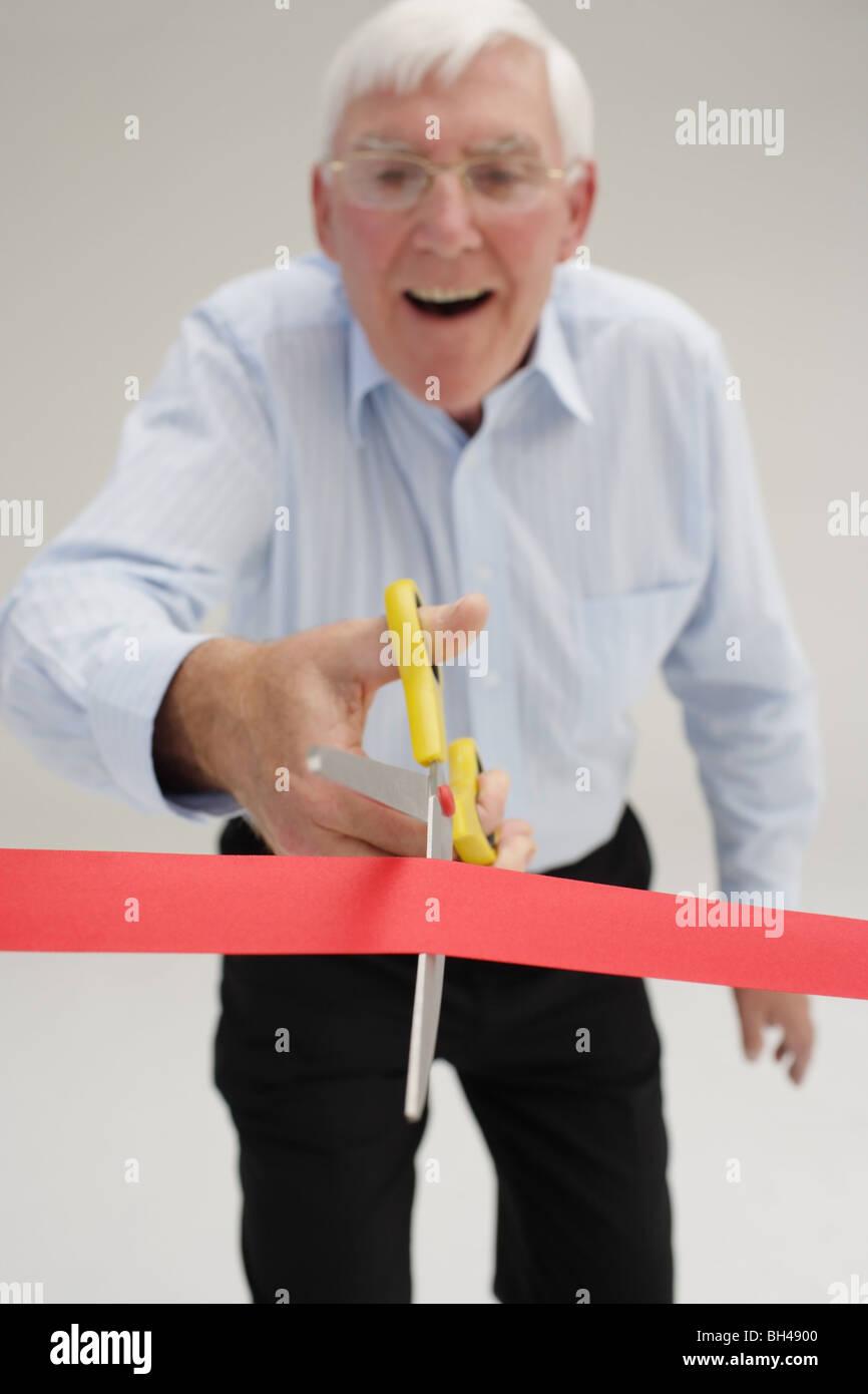 Empresario senior acerca de cortar a través de una cinta roja, riendo Imagen De Stock