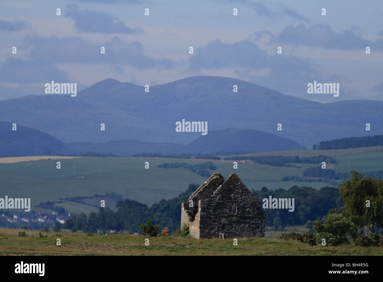 Abandonded cottage en Cromarty Firth con campos y montañas en el fondo. Foto de stock