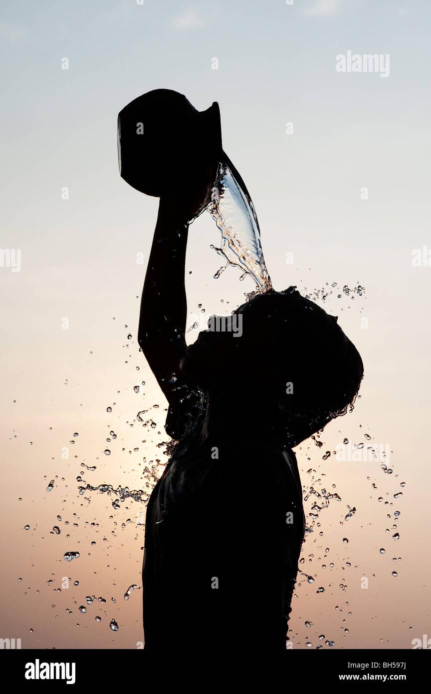 Niño Indio verter agua sobre sí mismo de una olla de barro silueta. Andhra Pradesh. La India Imagen De Stock