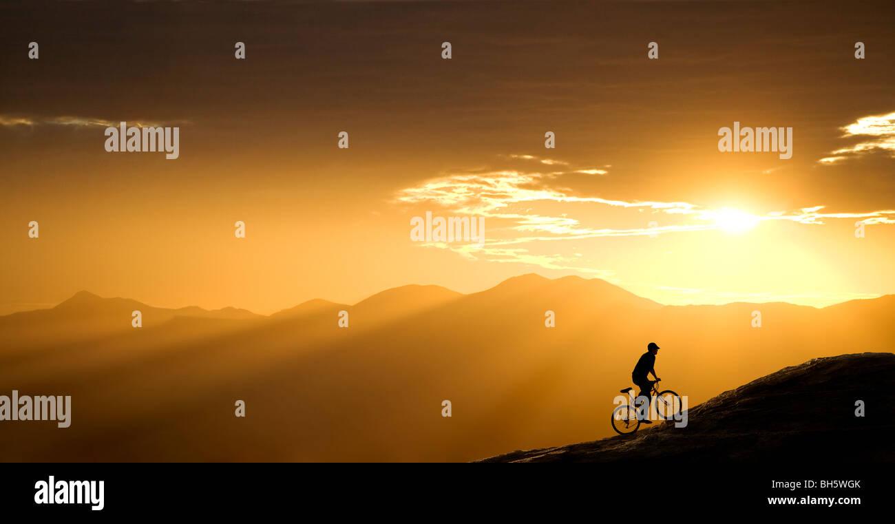 Ciclista de montaña sube por una colina al atardecer. Este está en Arizona, justo al oeste de Tucson. Imagen De Stock