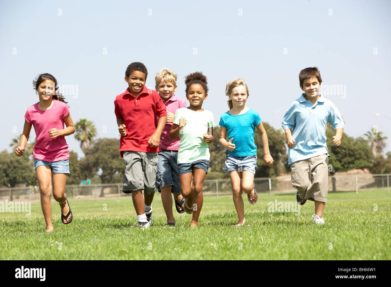 Un grupo de niños corriendo en el parque Foto de stock