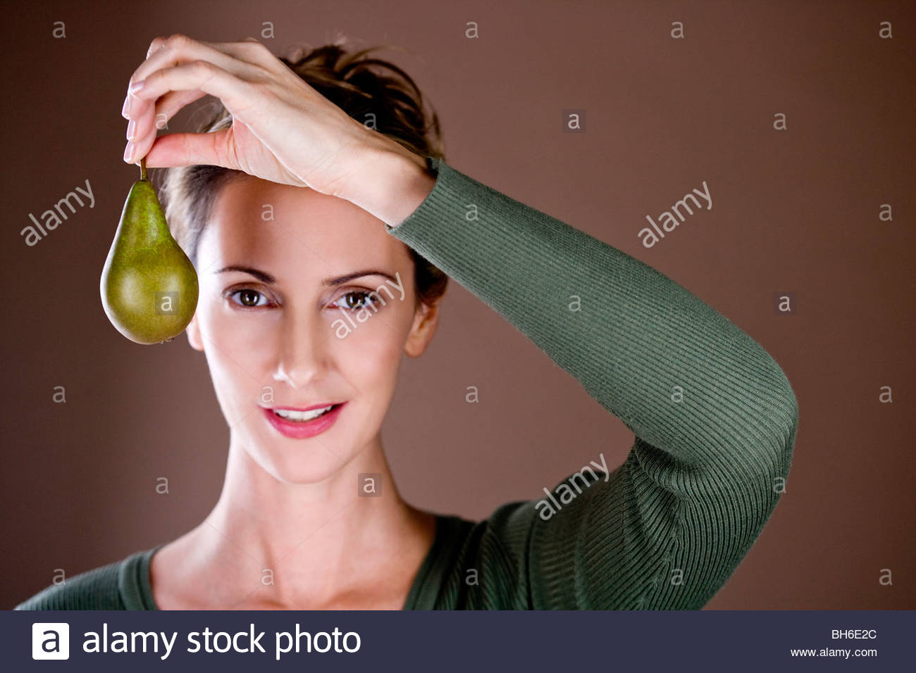Una mujer adulta media sosteniendo una pera Imagen De Stock