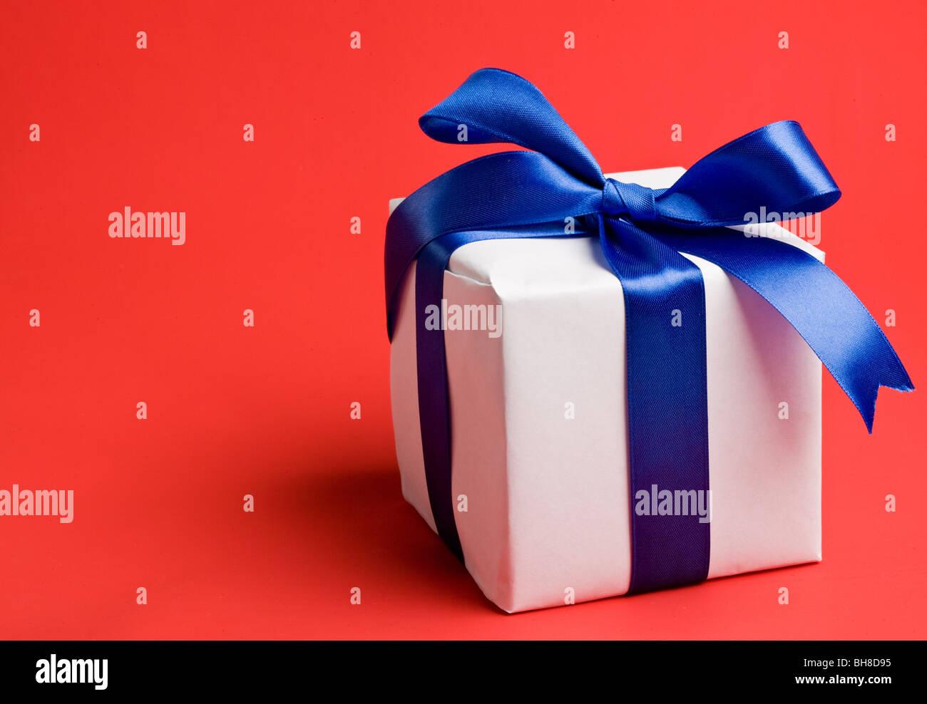 Regalo de color blanco con un lazo azul sobre un fondo rojo. Imagen De Stock