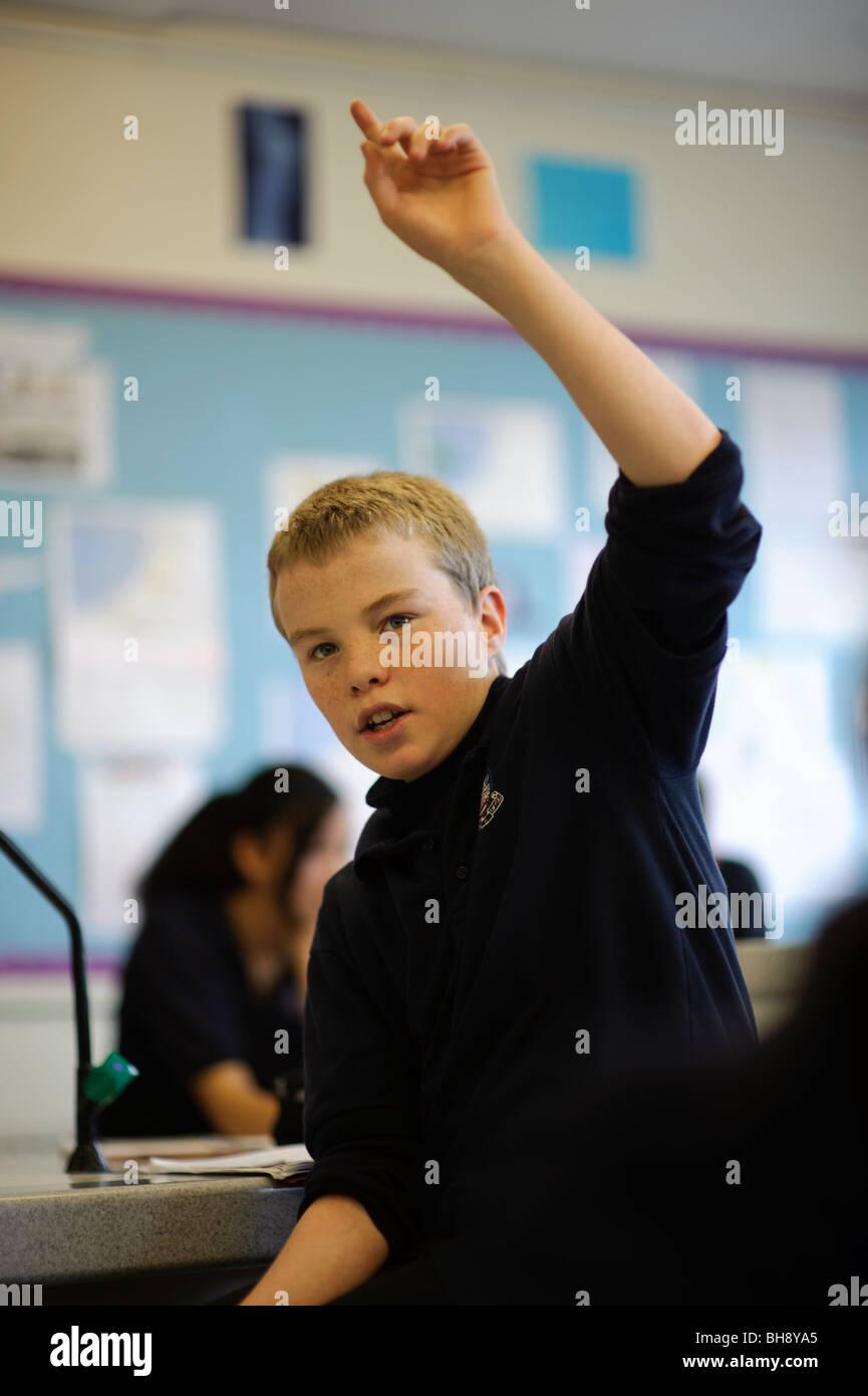Teenage colegial contestar la pregunta en la clase, la mano en el aire, escuela secundaria, UK Imagen De Stock