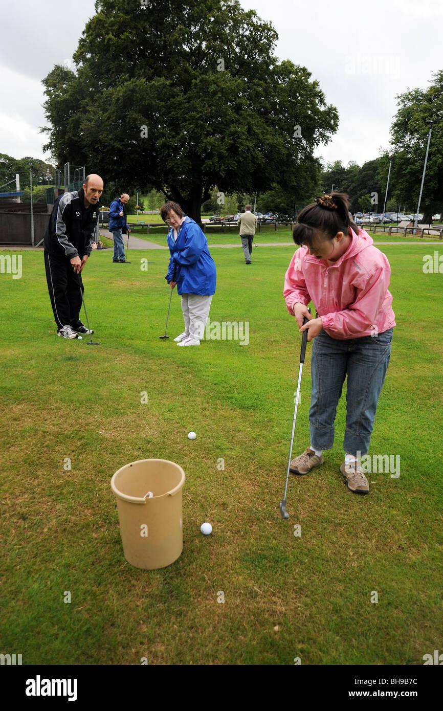 Dos mujeres con discapacidades de aprendizaje jugar pitch and putt, North Yorkshire Foto de stock