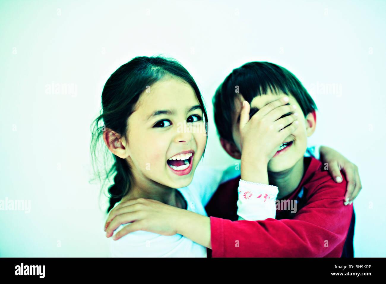 Niño de 7 años de edad y seis niñas jugando juntos sosteniendo la mano sobre los ojos Imagen De Stock