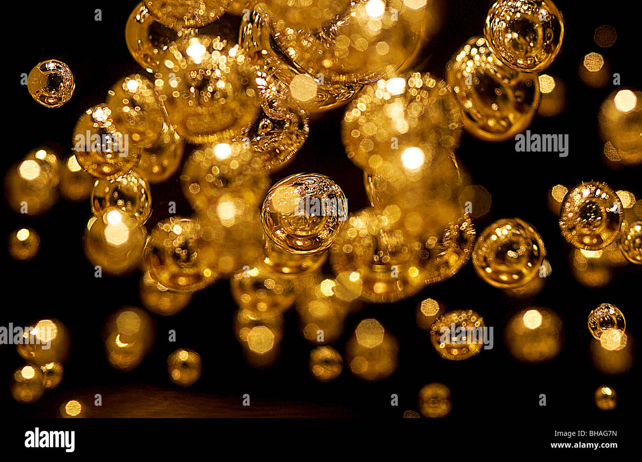 Burbujas de oro en un bloque de plástico transparente Imagen De Stock