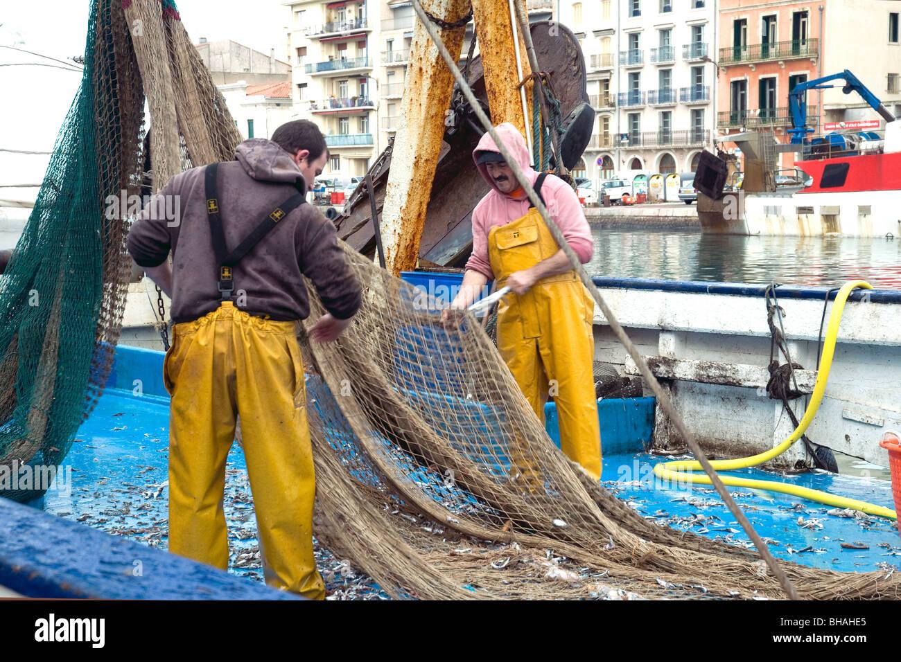 Los pescadores despejando su neta del arrastrero en Sète, Francia, el mayor puerto pesquero del Mediterráneo Foto de stock