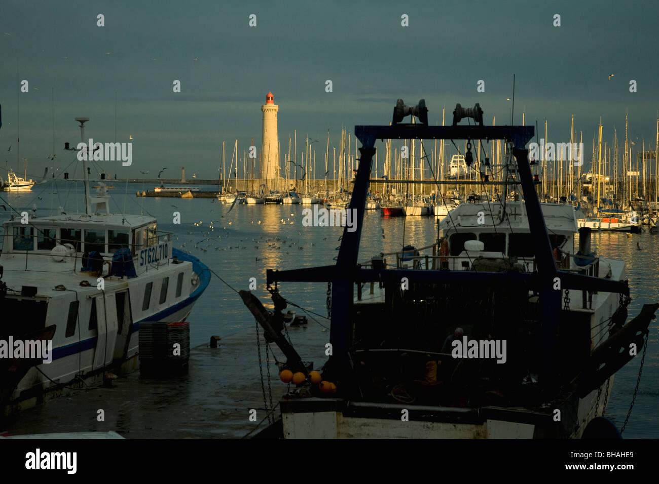 En Sète, Francia, el mayor puerto pesquero del Mediterráneo, los arrastreros están amarrados tranquilamente como el sol vespertino ilumina el faro Foto de stock