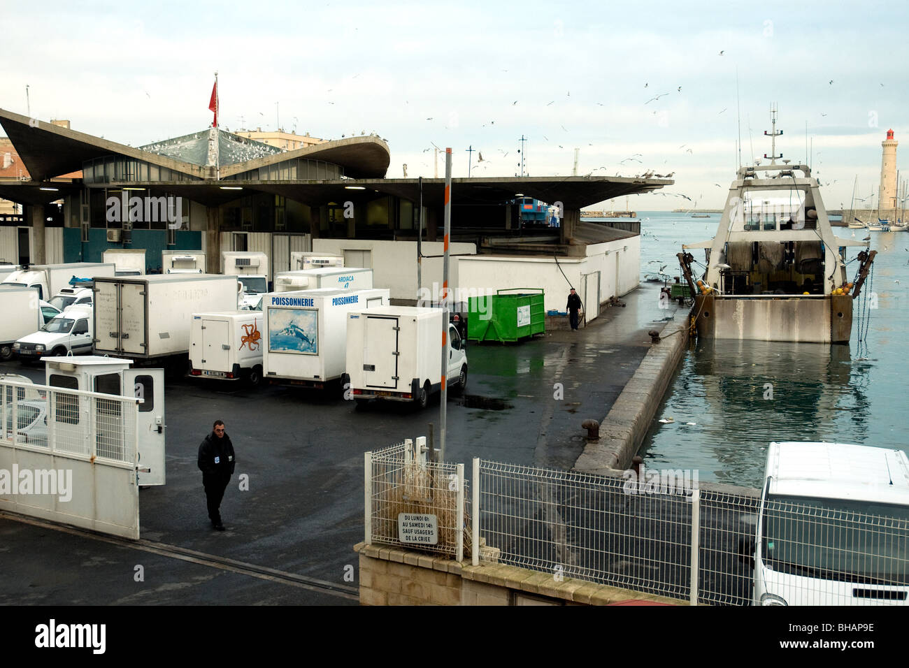 En Sète, Francia, el mayor puerto pesquero del Mediterráneo, un arrastrero moros junto a la subasta de pescado del puerto muelle cuando se aproxima la noche Foto de stock