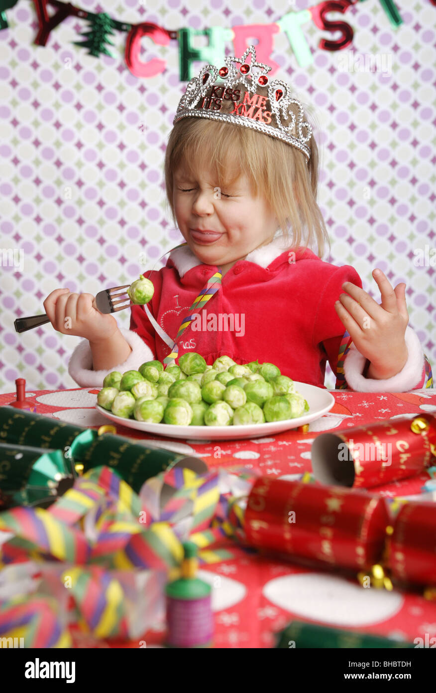 Un niño de 3 años sentado en una mesa con decoraciones de Navidad y un plato lleno de brotes tirando un Imagen De Stock