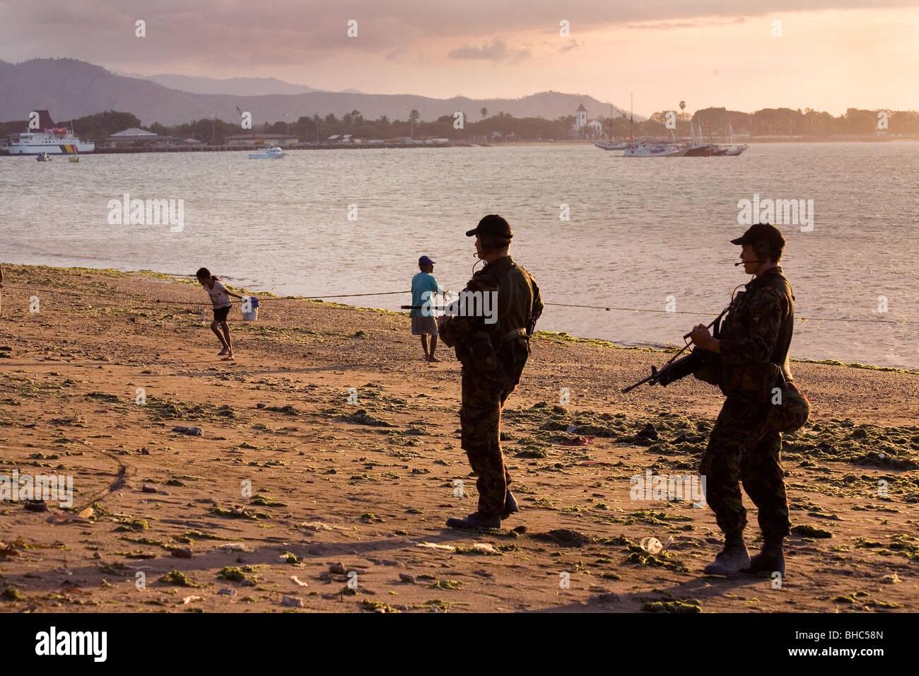 Onu soldados patrullan armadas Dili, Timor Oriental playa en el atardecer. Imagen De Stock