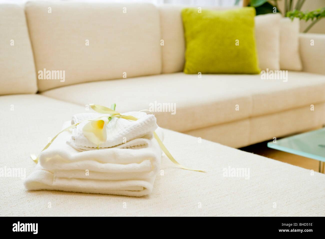 Toallas plegadas con Lily en el sofá Foto de stock