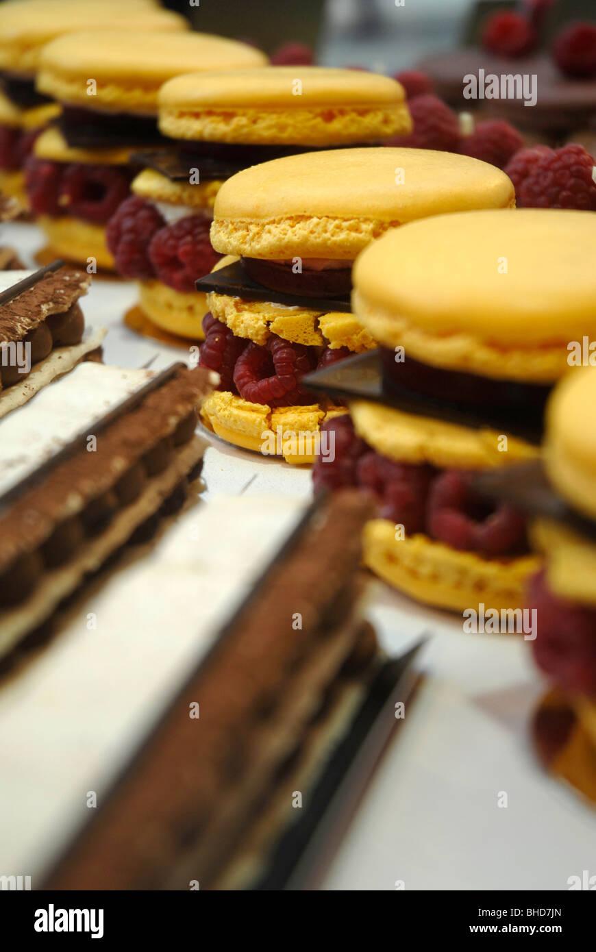 Dulces macarons superpuesto con frambuesas frescas y finas obleas de chocolate en el escaparate de la pantalla Imagen De Stock