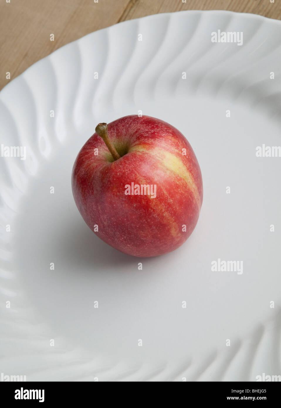 Comer manzana roja sobre placa blanca sobre la mesa de madera Imagen De Stock