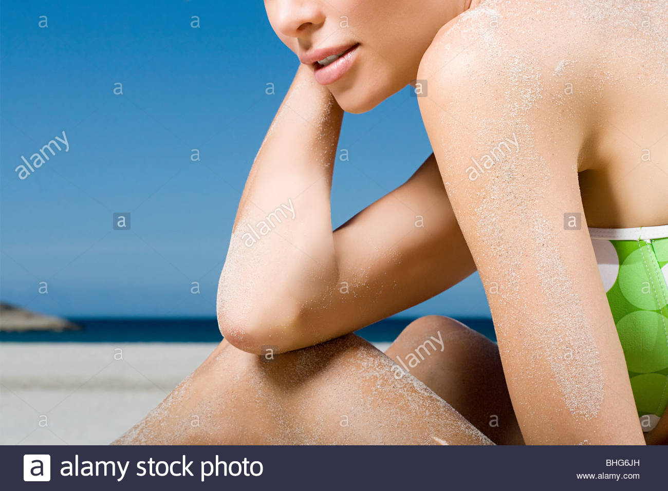 Ver sección media de mujer en la playa relajante Imagen De Stock