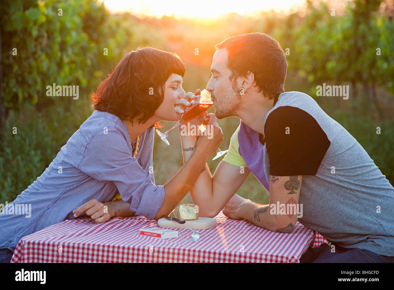 Par bebiendo vino en un campo Imagen De Stock