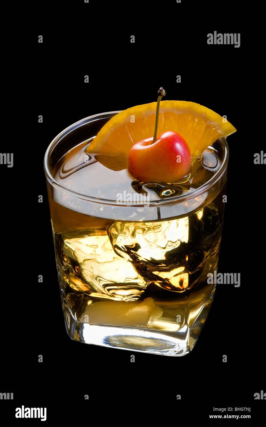 Antigua bebida mezclada con rodajas de naranja, cereza y Sugar Cube adorne sobre fondo negro con Imagen De Stock