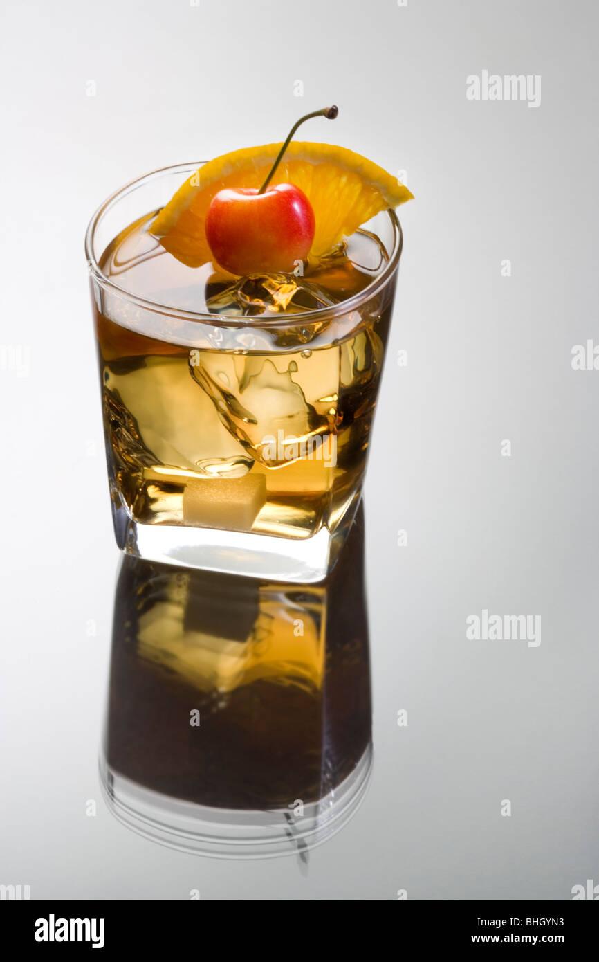 Antigua bebida mezclada con rodajas de naranja, cereza y Sugar Cube adorne sobre fondo gris con reflexión Imagen De Stock