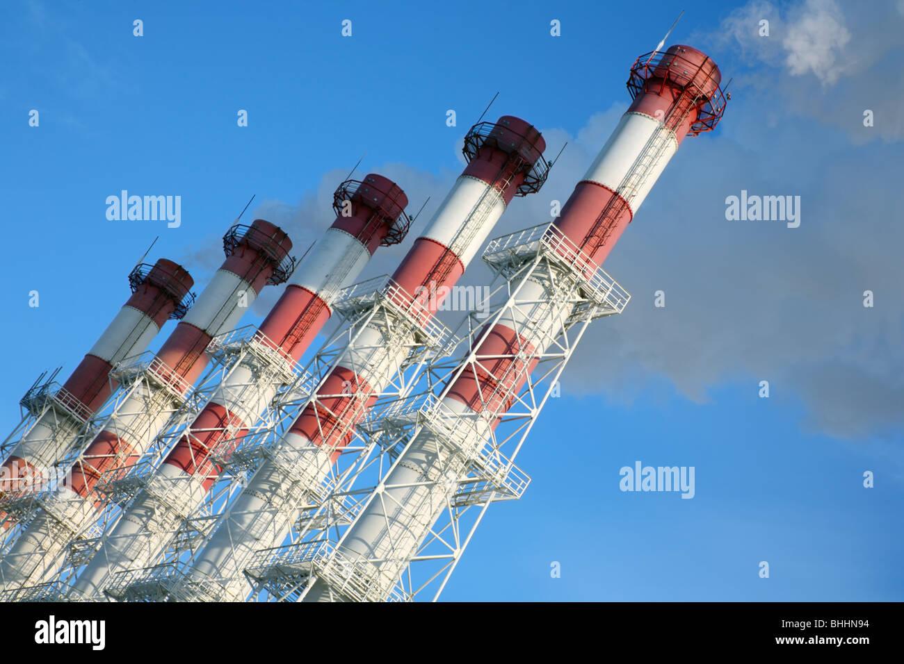 Cinco chimeneas con vapor sobre un fondo de cielo azul. Inclinar la vista. Imagen De Stock