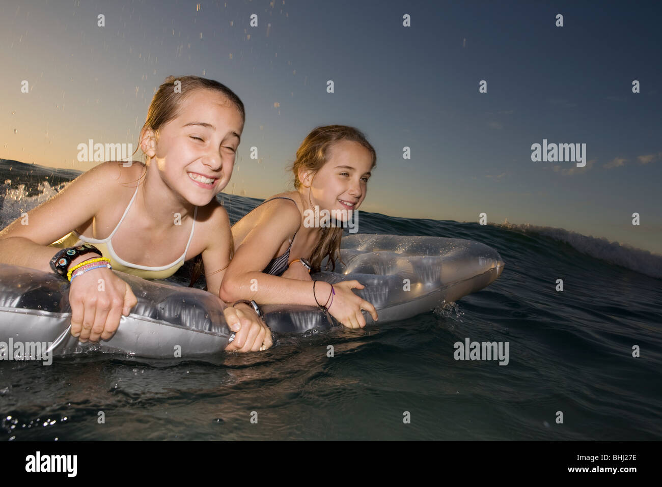 Hermanas gemelas wave surf en airbed Foto de stock
