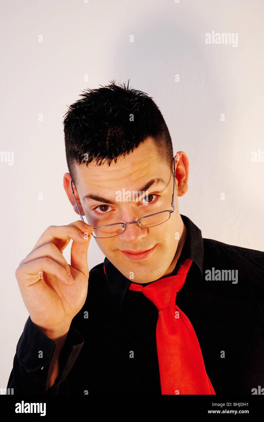 Joven de llevar gafas, sonriendo y mirando a la cámara. Imagen De Stock