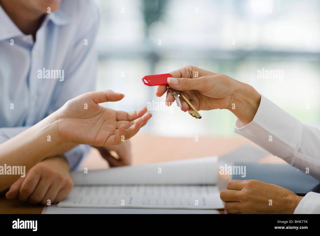 Recepcionista de hotel entrega la llave de la habitación para los huéspedes Foto de stock