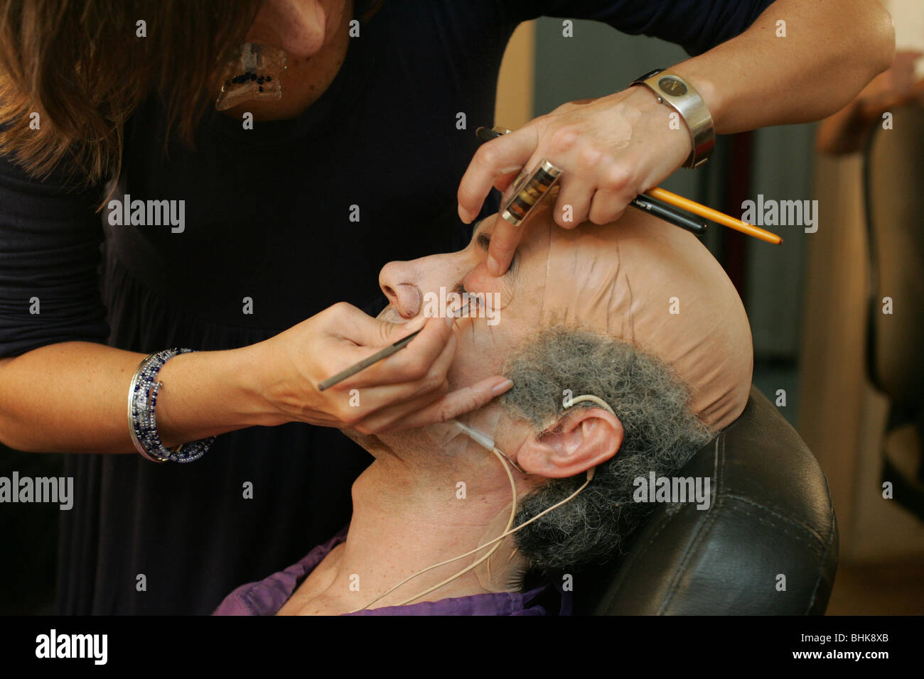 Maquillaje artista aplicar delineador de ojos para un actor. Imagen De Stock