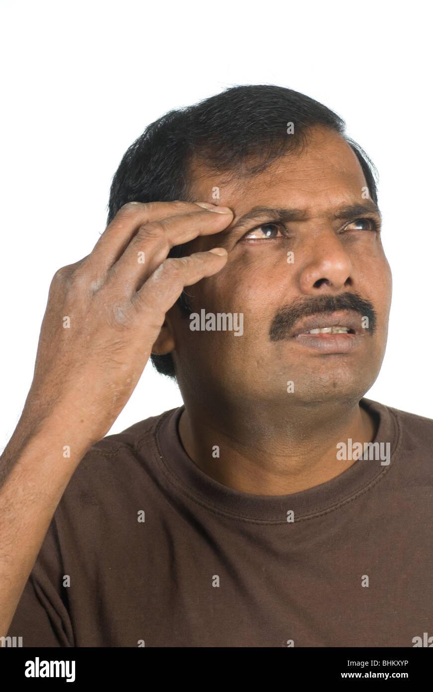 Hombre indio intenta recordar algo con la mano sobre la cabeza contra un fondo blanco. Imagen De Stock