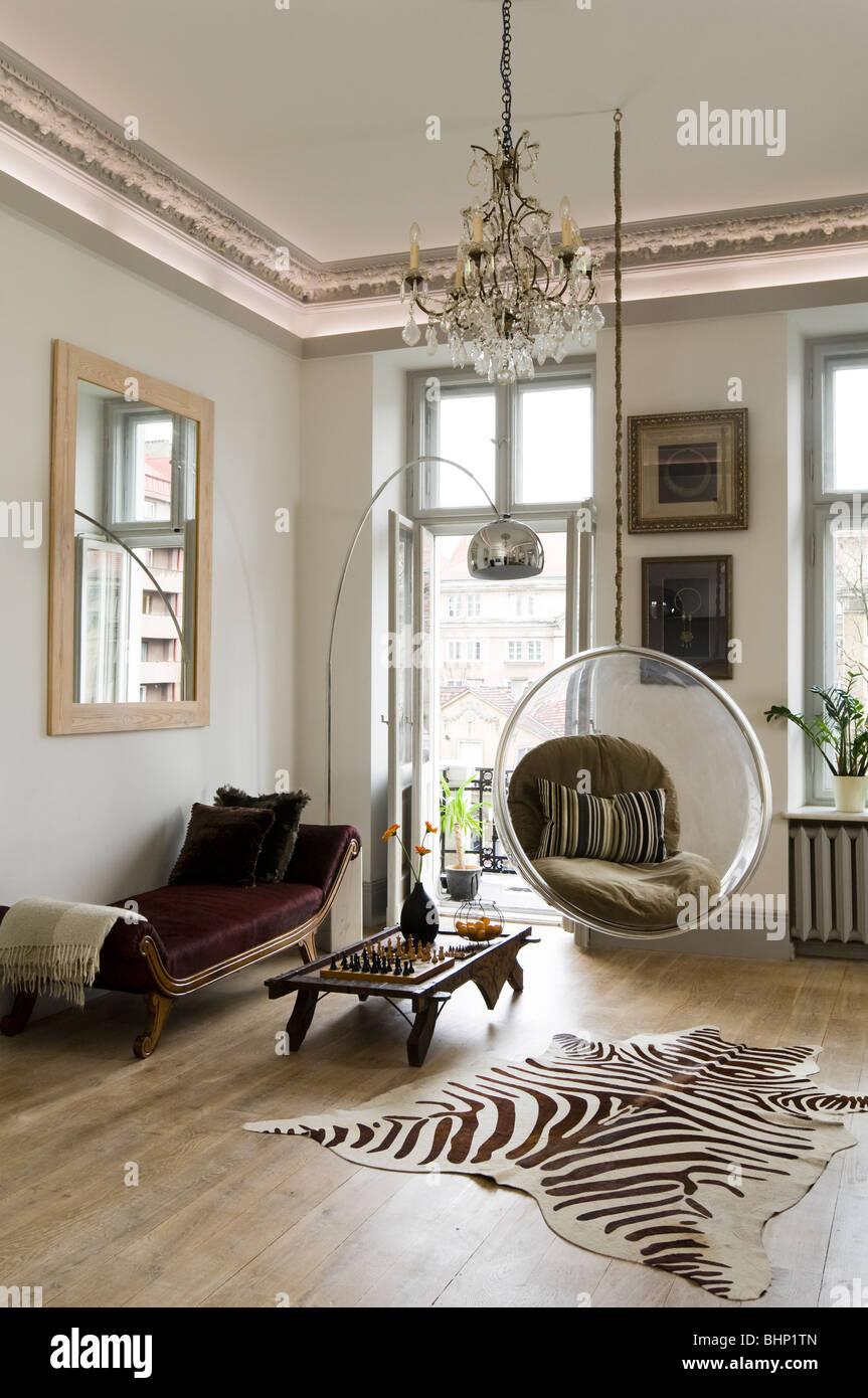 Eero Aarnio silla burbuja en la sala de estar con una alfombra de piel de cebra y una lámpara de araña Imagen De Stock