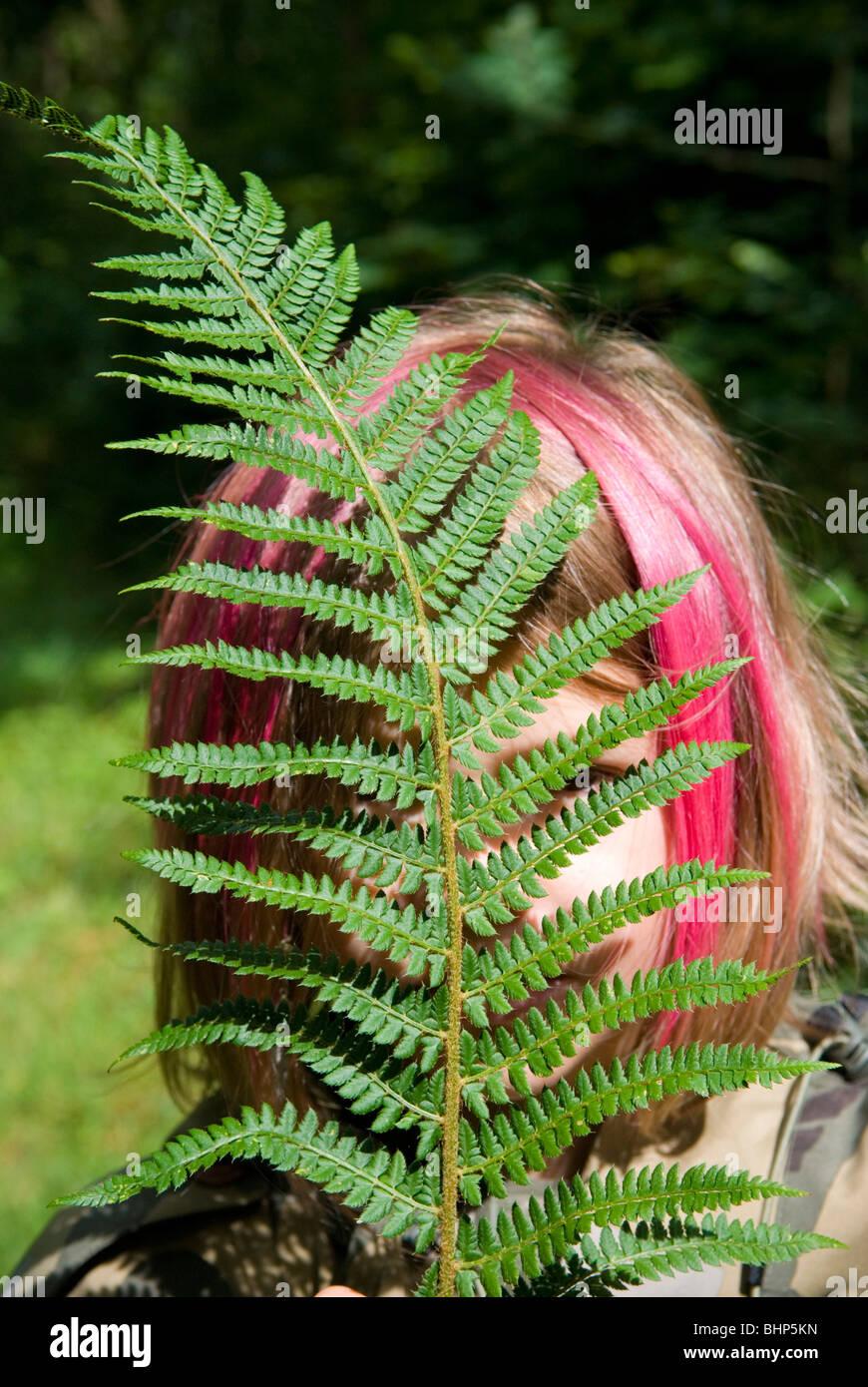 Una joven con el cabello teñido de rosa bob se esconde detrás de una hoja de helecho verde brillante que Imagen De Stock