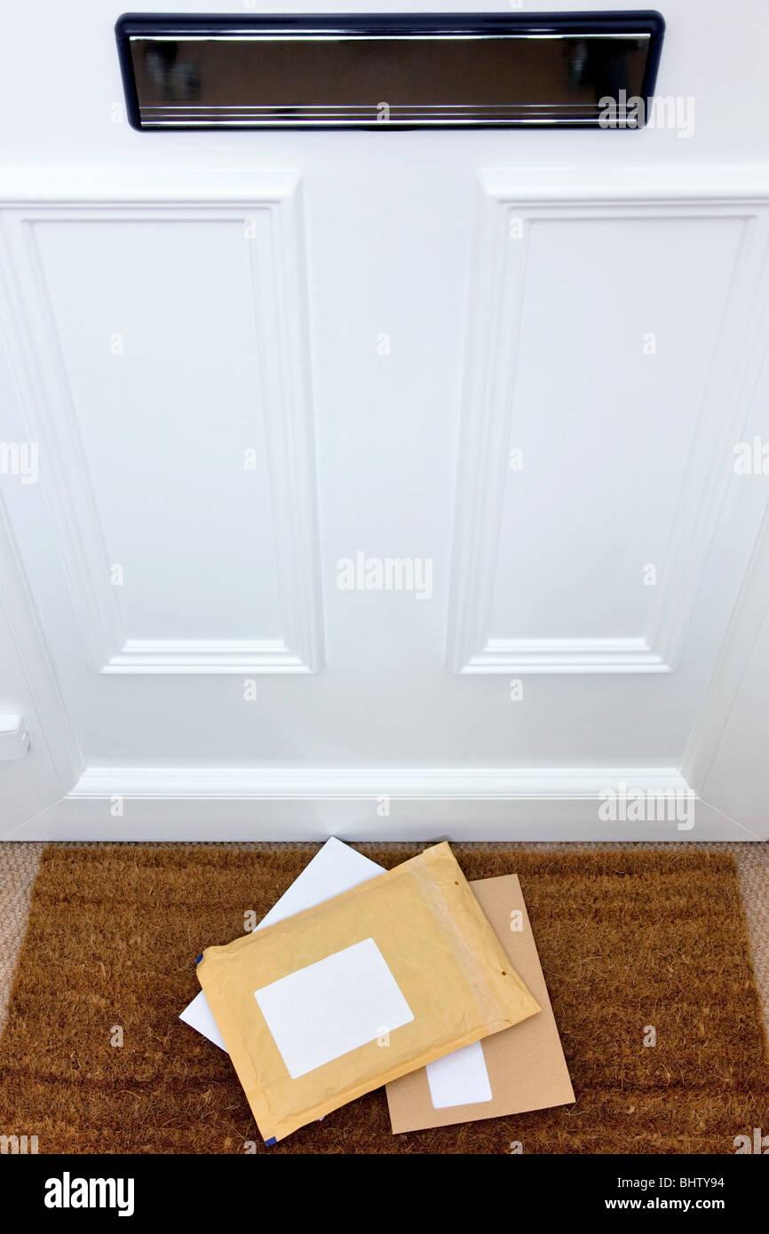 Cartas y un paquete tumbado sobre un felpudo, etiquetas en blanco para añadir su propio nombre y dirección, Imagen De Stock