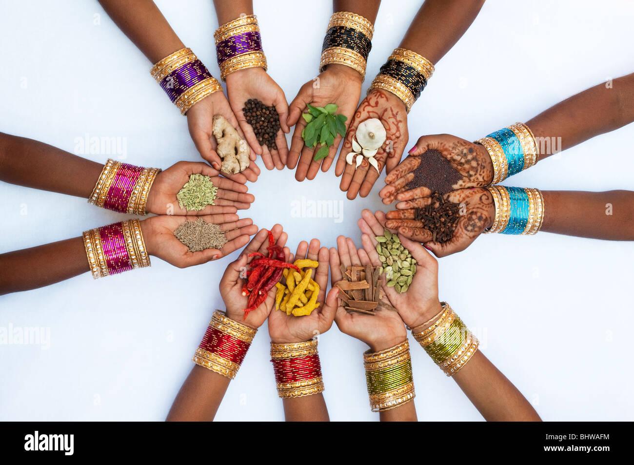 Los niños indios manos sosteniendo diversas especias de cocina india sobre fondo blanco. Imagen De Stock