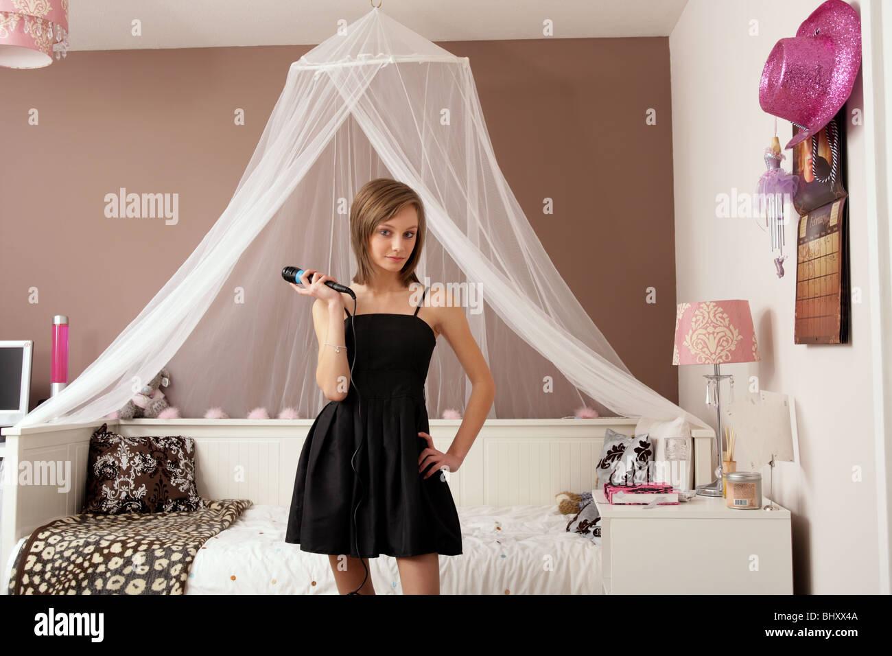 Una rubia de catorce años de edad, niña de pie en su dormitorio sosteniendo un micrófono y que llevaba Imagen De Stock