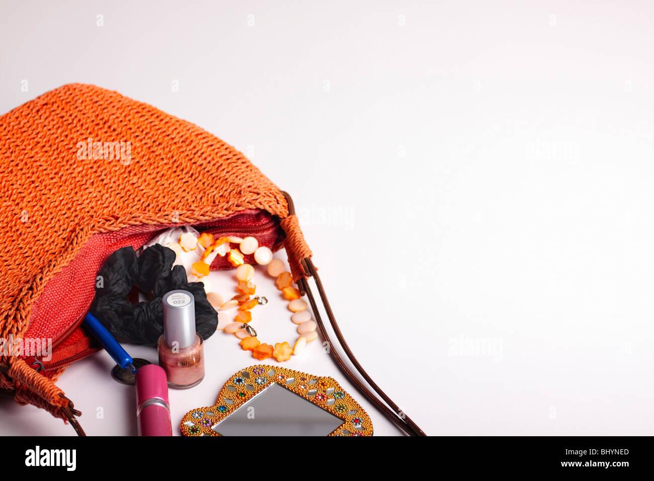 93879f2da Moderna, tejida de fibra de naranja bolso sobre su costado, derramando su  contenido.