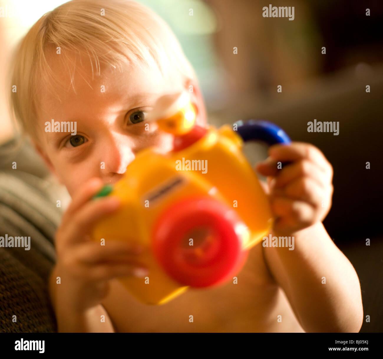 Niño jugando con la cámara de juguete. Imagen De Stock