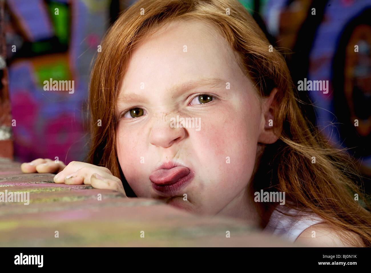 Retrato de muchacha detrás del muro fuera la lengua Imagen De Stock