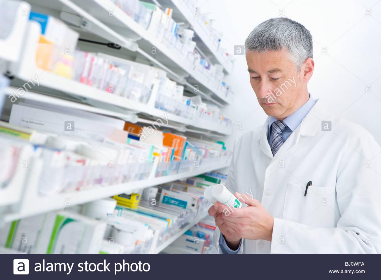 Lectura farmacéutico botella de medicamento en la farmacia Imagen De Stock