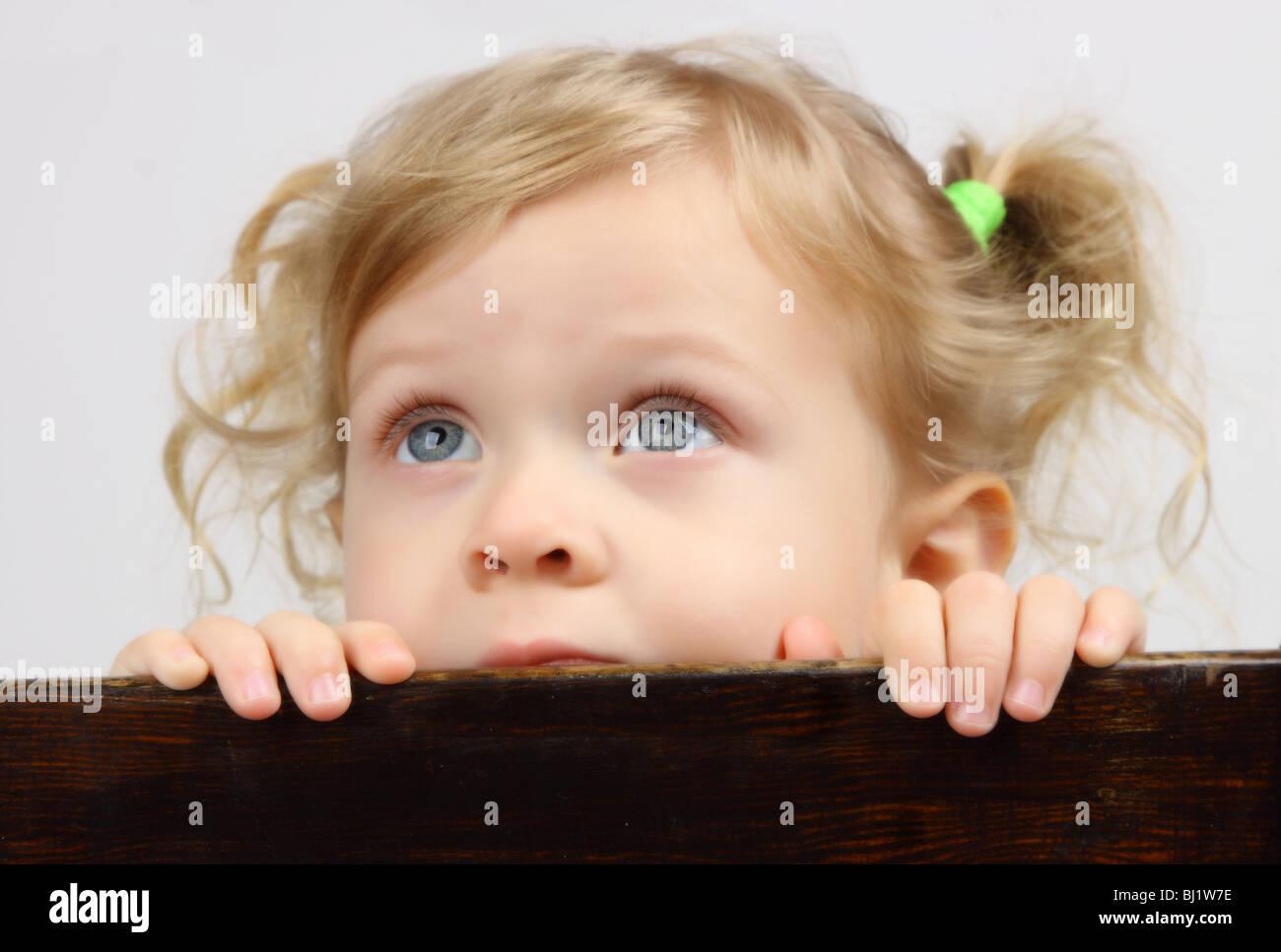 Un niño de 3 años rubia niña mirando hacia la parte posterior de la silla. 48c4600d06a