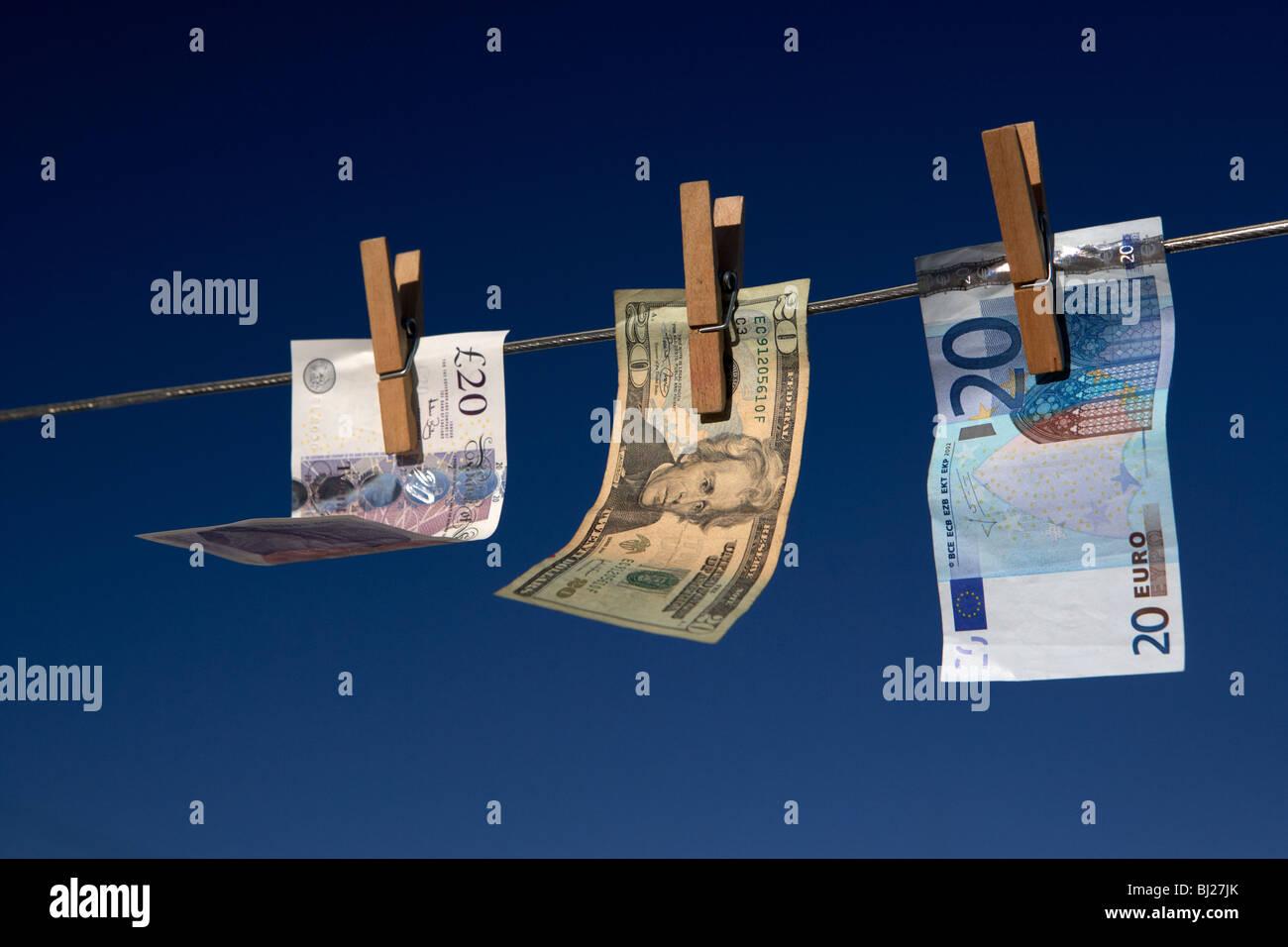Veinte libras de dólares billetes colgando de una línea de lavado con el cielo azul Foto de stock
