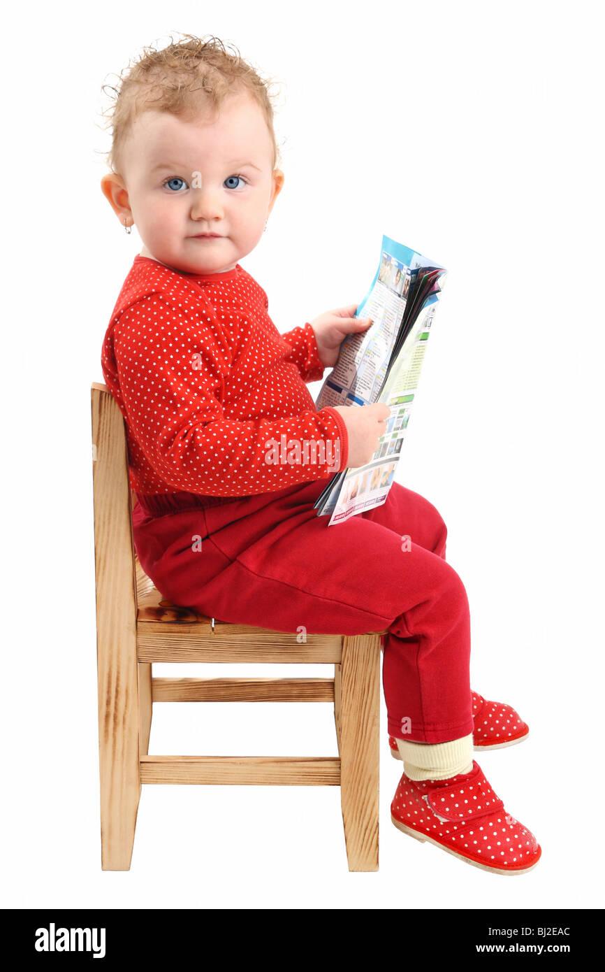 8b75d3181 Niña vestida de rojo sentado en una silla leyendo una revista mirando a la  cámara aislado