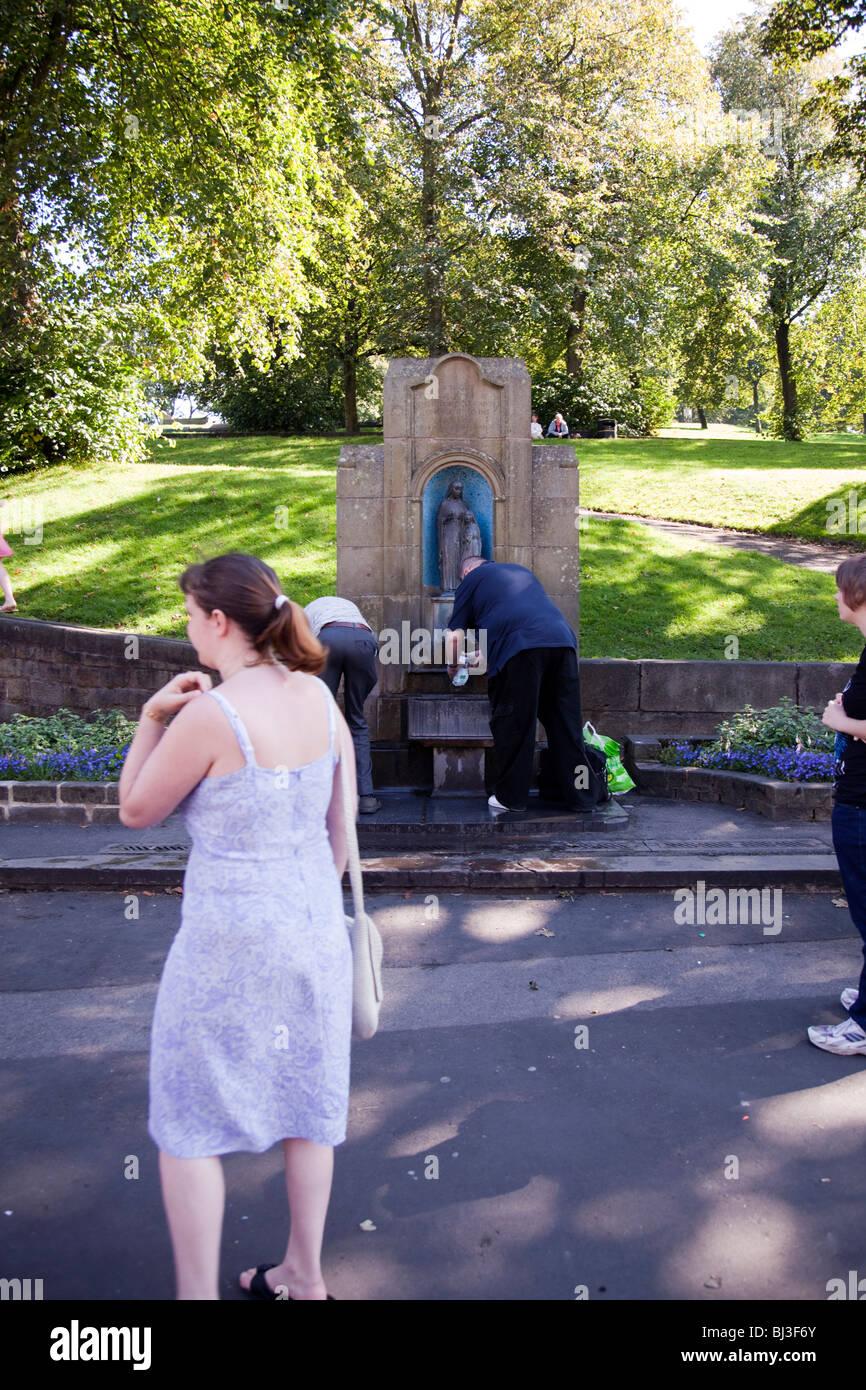 Los lugareños en Buxton, Derbyshire, Inglaterra, recoger agua de un tubo de soporte en la calle para el agua de Foto de stock