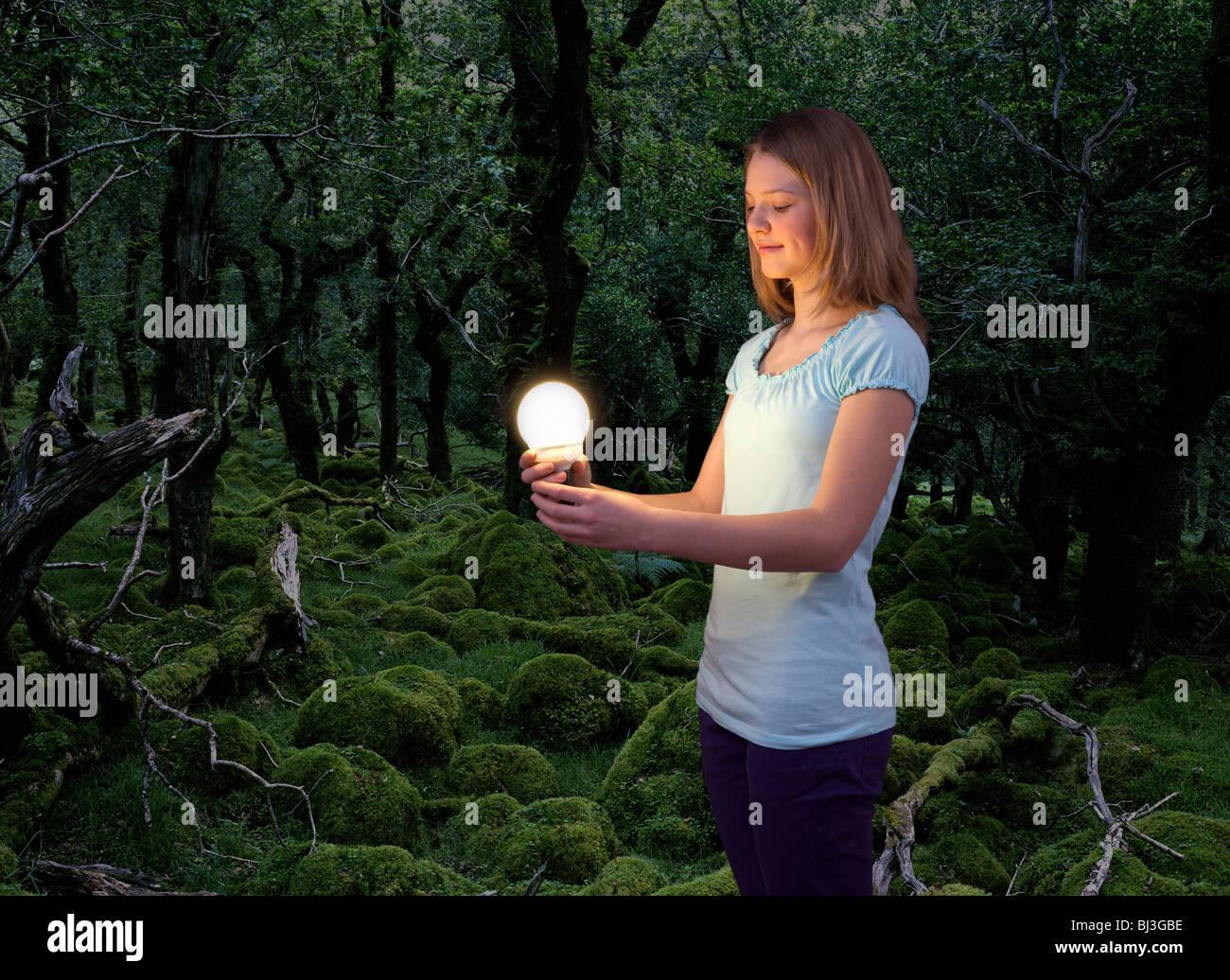 Chica con bombilla de ahorro de energía Imagen De Stock