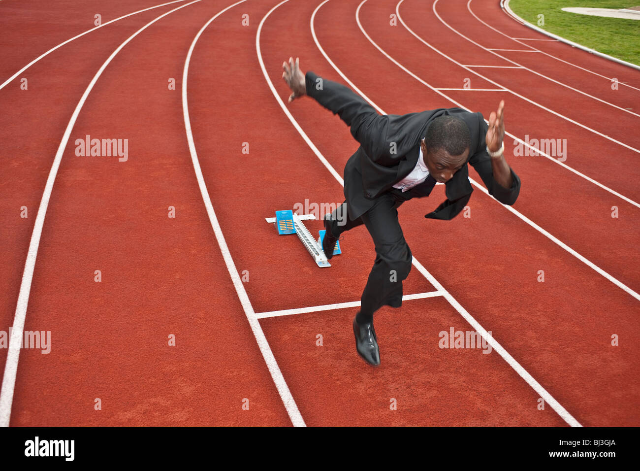 Empresario esprintar en pista de atletismo Imagen De Stock