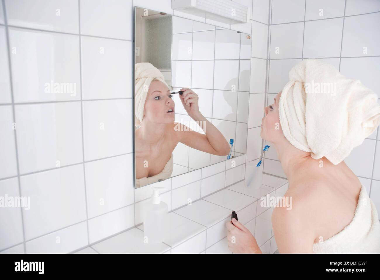 Las mujeres poniendo en mascara delante del espejo del baño Imagen De Stock